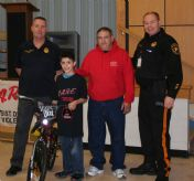 ACSSS Student Chandler recieves a bicycled donated by Greg Depiano with Toys for Kids
