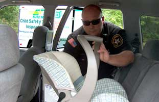 Officer installing child safety seat in car